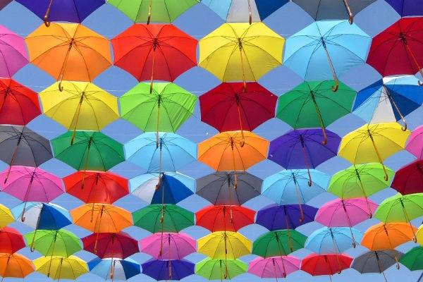 Mängder med paraplyer i olika färger upphängda på linor med den ljusblå himlen i bakgrunden.